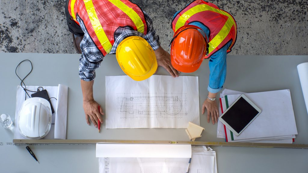 Top view of group of engineering team is meeting, planning construction work,looking paper plans at construction site,overhead view canada's construction industry